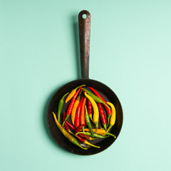 Fresh red, orange and green hot chilli peppers on a vintage frying pan. Studio shot isolated on mint background.