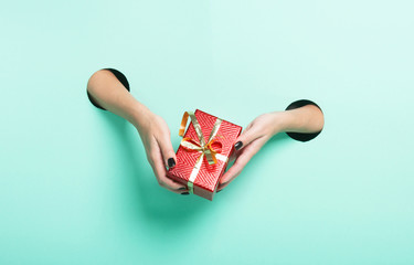 Female hands hold red gift through a hole on neon mint background.