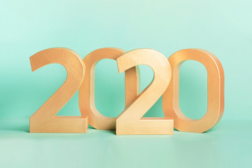 Golden new year 2020 number digits isolated on neon mint background. Studio shot.