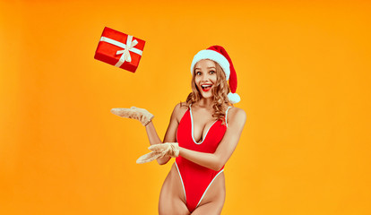 Image on isolated yellow background of young woman catch falling red Christmas gift box. Smiling excited sexy girl in red lingerie and Santa hat wearing warm gloves waiting for New Year surprise