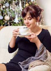Beautiful girl drinking coffee sitting in chair near christmas tree. Festive comfy evening in home.