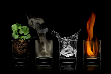 Four elements concept in glasses. earth, air, water, fire.