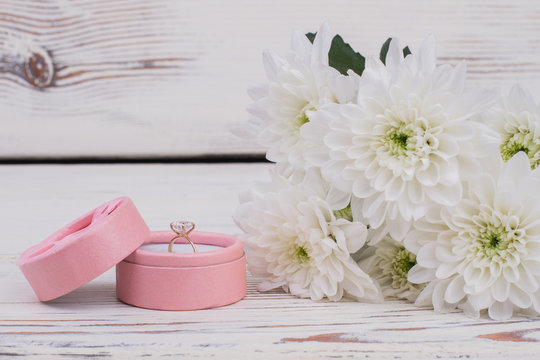 Engagement ring in box and bouquet of flowers. Jewelry box with diamond ring and bunch of white chrysanthemums. Love and romance concept.