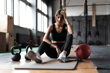 Poster Fitness Young woman sitting on floor after her workout and looking down. Female athlete taking rest after fitness training
