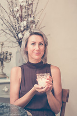 Toned picture of beautiful blonde lady sitting in cafe or restaurant holding candle