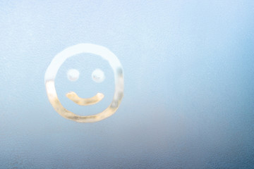 Smiling face painted on a frozen window, winter fun, season change and hope concept, place for text, copyspace