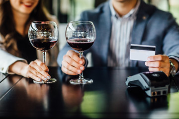 Picture showing people paying in restaurant by credit card reader, with two glasses of wine.