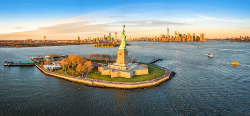 Wall Mural - Aerial panorama of the Statue of Liberty in front of Jersey City and New York City skylines at sunset.