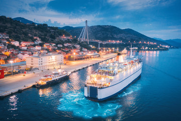 Aerial view of cruise ship in port at night. Landscape with ships and boats in harbour, city lights, buildings, mountains, blue sea at sunset. Top view. Luxury cruise. Floating liner at harbor in dusk