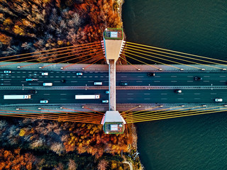 Beautiful panoramic aerial drone view to cable-stayed Siekierkowski Bridge over the Vistula river and Warsaw City skyscrapers, Poland in gold red autumn colors in November evening at sunset - top down