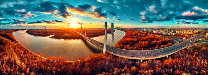 In de dag Bruggen Beautiful panoramic aerial drone view to cable-stayed Siekierkowski Bridge over the Vistula river and Warsaw City skyscrapers, Poland in gold red autumn colors in November evening at sunset