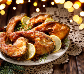 Christmas carp, Fried carp fish slices on a ceramic plate on the holiday table, close up....
