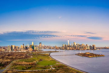 Wall Mural - Aerial view of New York City and Jersey City skylines together with Ellis Island, as viewed from above Liberty State Park, in New Jersey, at dusk.