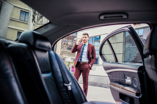 Man in suit speaking on mobile near the luxury car