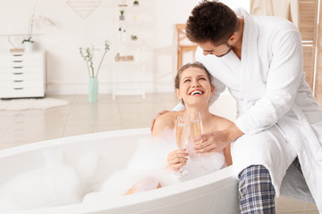 Happy young couple drinking champagne in bathroom