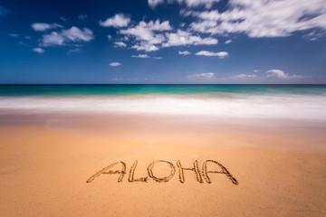 The word aloha written on the sand of a beach in Kauai, Hawaii