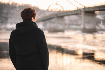 Back view of thoughtful young man looking at river while standing outdoors in winter Fotomurales
