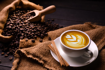 Foto op Canvas Cafe Cup of coffee latte and coffee beans in burlap sack on old wooden background