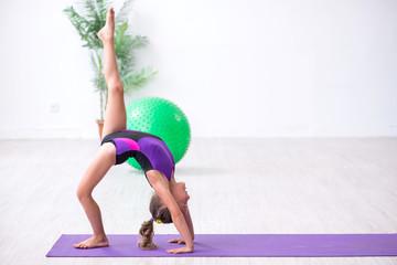 Little girl gymnast doing exercises indoors