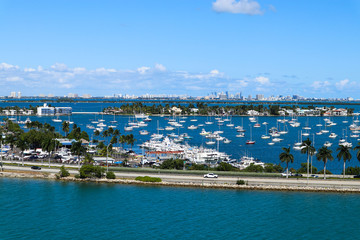 MacArthur Causeway, with moored vessels, Palm Island and Miami Beach hotels and condos in South Beach, Miami, Florida.