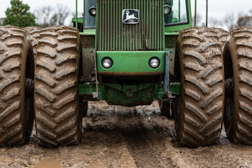 Spring Grove, IL/USA – December, 1 2019: Closeup front view of John Deere tractor in field with muddy tires