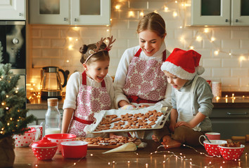 happy family mother and children bake christmas cookies.