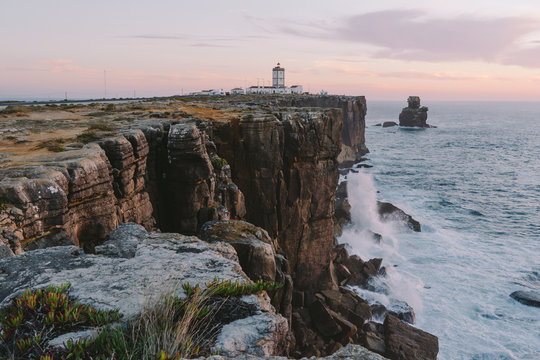 Lighthouse on the edge of a cliff big ocean waves crash on a rock Peniche Portugal