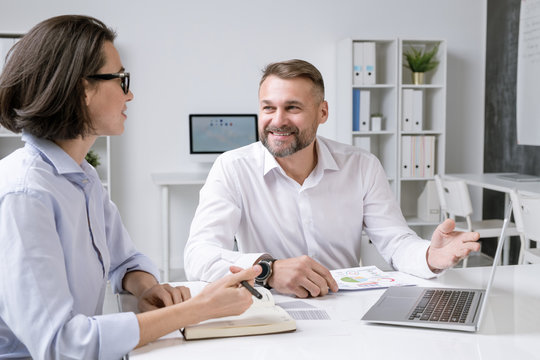 Happy male broker pointing at laptop display while making presentation