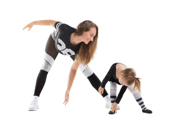 Young mother is practicing fitness with little daughter isolated at white background.