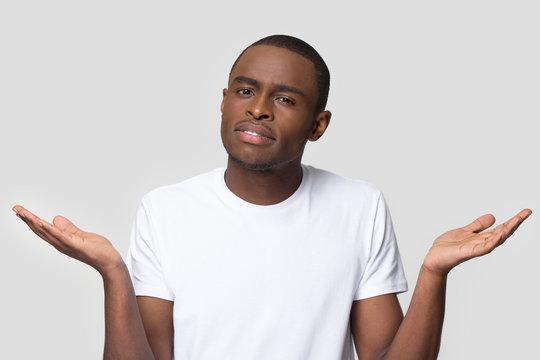 Confused African American man shrugging shoulders, looking at camera