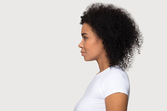 Young attractive African American woman standing in profile isolated
