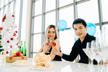 Happy Asian man and woman smiling and looking at camera while sitting at banquet table and clinking glasses of wine during Christmas celebration