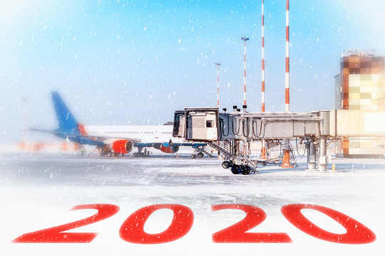 winter 2020 airport landscape with white snow apron and airplane parked to gate against blue sky background. Ground view of passenger jet aircraft. Winter season holiday air travel. Creative blur
