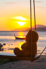lonely Teddy Bear sitting on a swing in front Rawai beach to see sunrise.