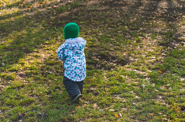 A little guy in a green knitted hat walks in the park in frosty weather. A child having fun by running on the grass. Walk. Back view