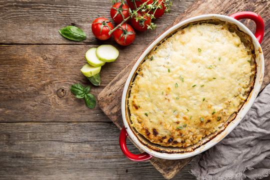 Casserole with chicken and zucchini on old wooden background, top view