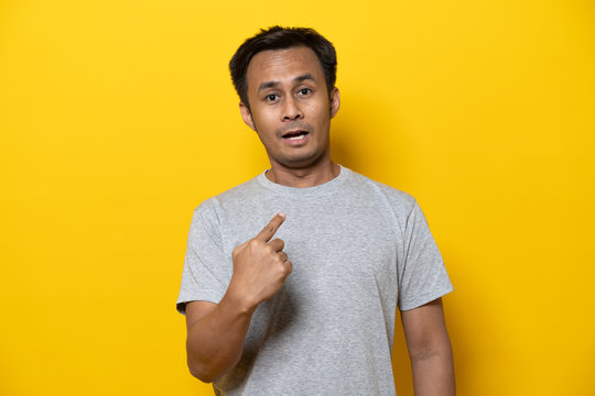 Amazed young man pointing at himself and have a surprised facial expression isolated on yellow background in studio.
