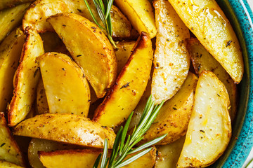 Baked potato wedges with rosemary in blue dish, top view. Healthy vegan food concept.