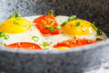 Fried eggs with tomatoes and green onions in gray pan.