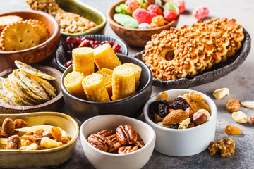 Variety of snacks and sweets on gray background. Waffles, nuts, sweets, cookies, chips and fruits.