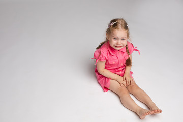 Stock photo of sweet little girl with braids in pink dress crying while sitting on the floor with bare feet. She is looking at the camera while sobbing.