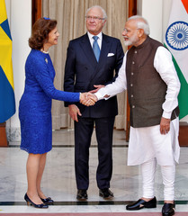 Sweden's Queen Silvia shakes hands with India's Prime Minister Narendra Modi as King Carl XVI Gustaf looks on during a photo opportunity ahead of their meeting at Hyderabad House in New Delhi