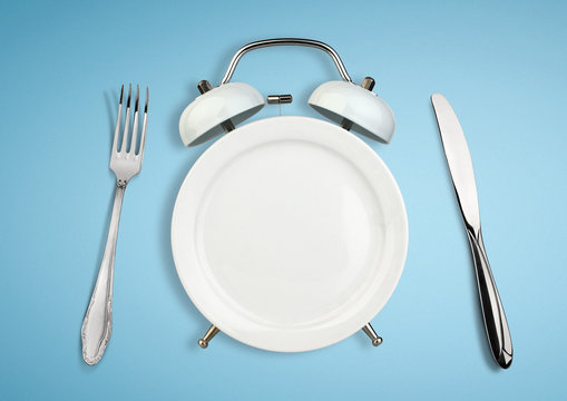 Concept of intermittent fasting, diet and weight loss. Plate as Alarm clock