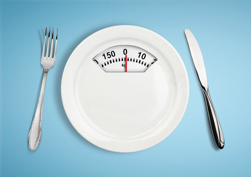 Diet and weight loss concept. Plate with scale weighing-machine