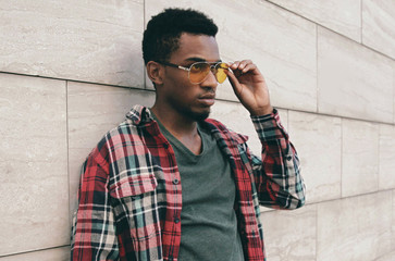 Wall Mural - Portrait close up of stylish african man wearing sunglasses, red plaid shirt, guy posing on city street over gray brick wall background