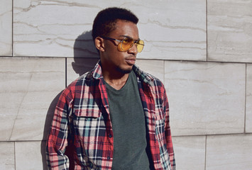 Wall Mural - Portrait of stylish african man wearing sunglasses, red plaid shirt, guy looking away posing on city street over gray brick wall background