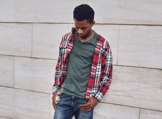 Wall Mural - Young african man wearing casuals, red plaid shirt on city street over gray brick wall background