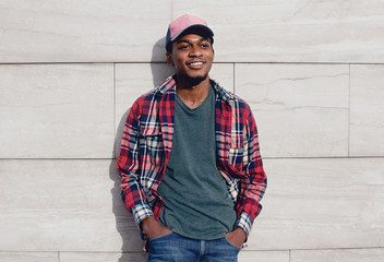 Wall Mural - Young smiling african man wearing casuals, red plaid shirt, baseball cap on city street over gray brick wall background