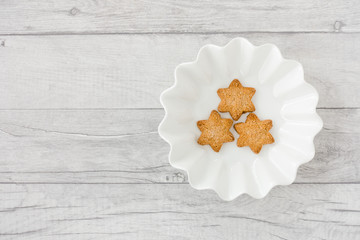 Star Shaped Christmas Cookies in Bowl on Wood Background