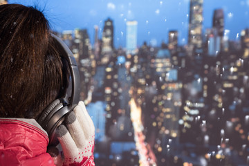 Young woman in a winter jacket and knitted gloves listening music in the headphones on roof of building of night New York at snowfall. Aerial and panorama view of skyscrapers of New York City.